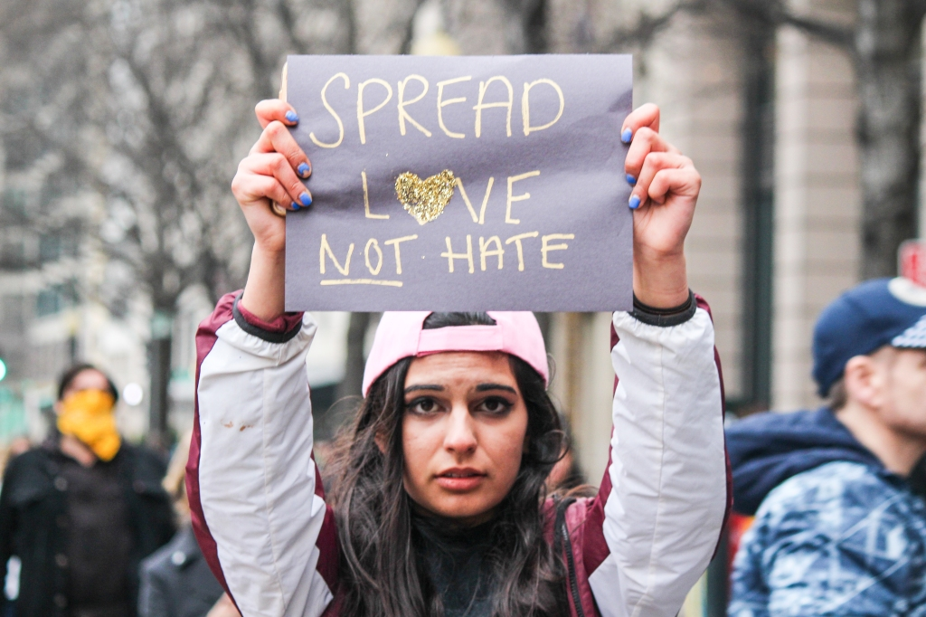 Woman holding sign that reads 'Spread love, not hate'