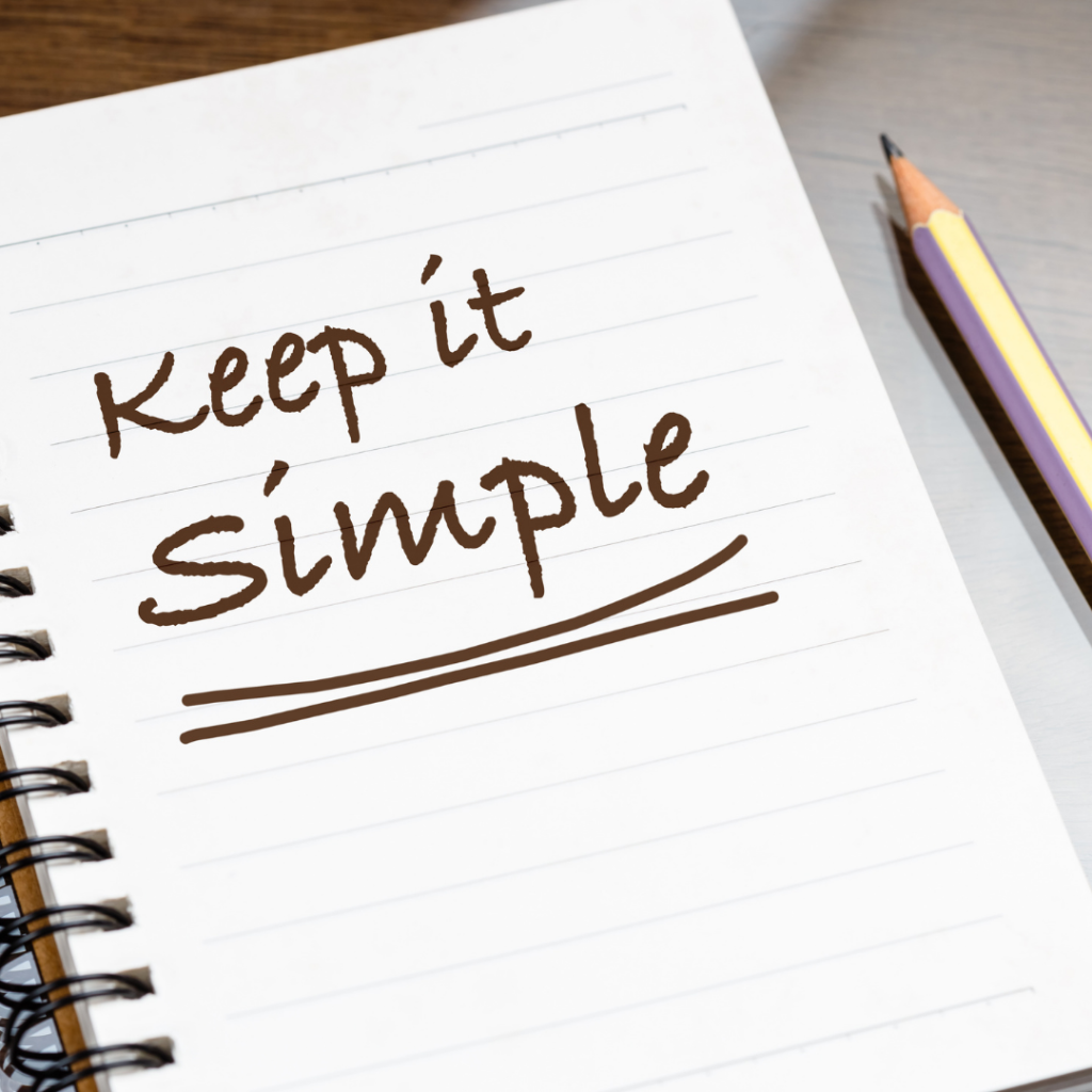A notebook with a pencil next to it. Text written on notebook reads 'Keep it simple'
