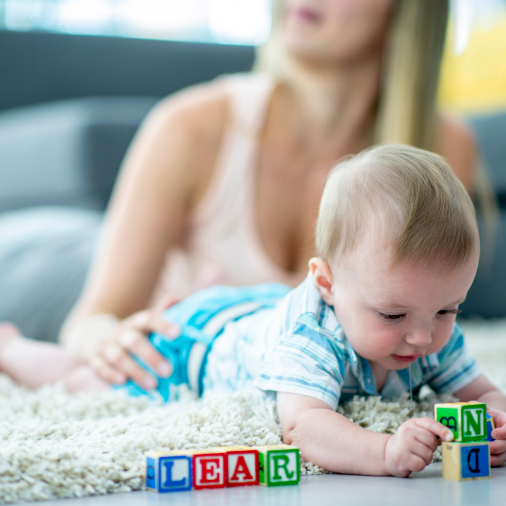 Baby boy playing with letter blocks that are arranged to spell 'learn', while mom sits behind.