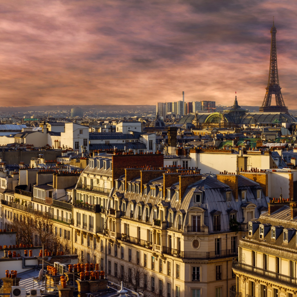 A picture of the roofs of Paris, at dusk, with the Eiffel Tower in the background.