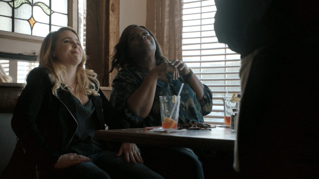 A picture from the Good Girls TV show - Annie and Ruby are sitting at a cafe table with half empty glasses, smirking at someone standing in front of them