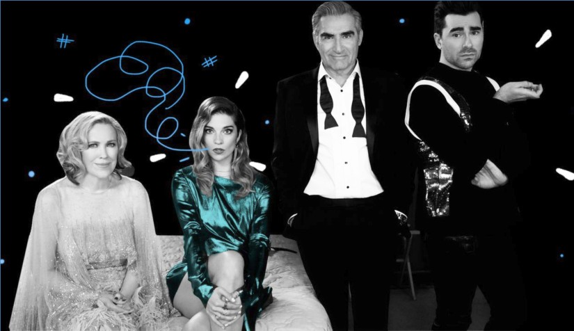 A decorative image with the cast of Schitt's Creek - the Rose family. Alexis and Moira are sitting on a bed, while Johnny and David are standing next to them.