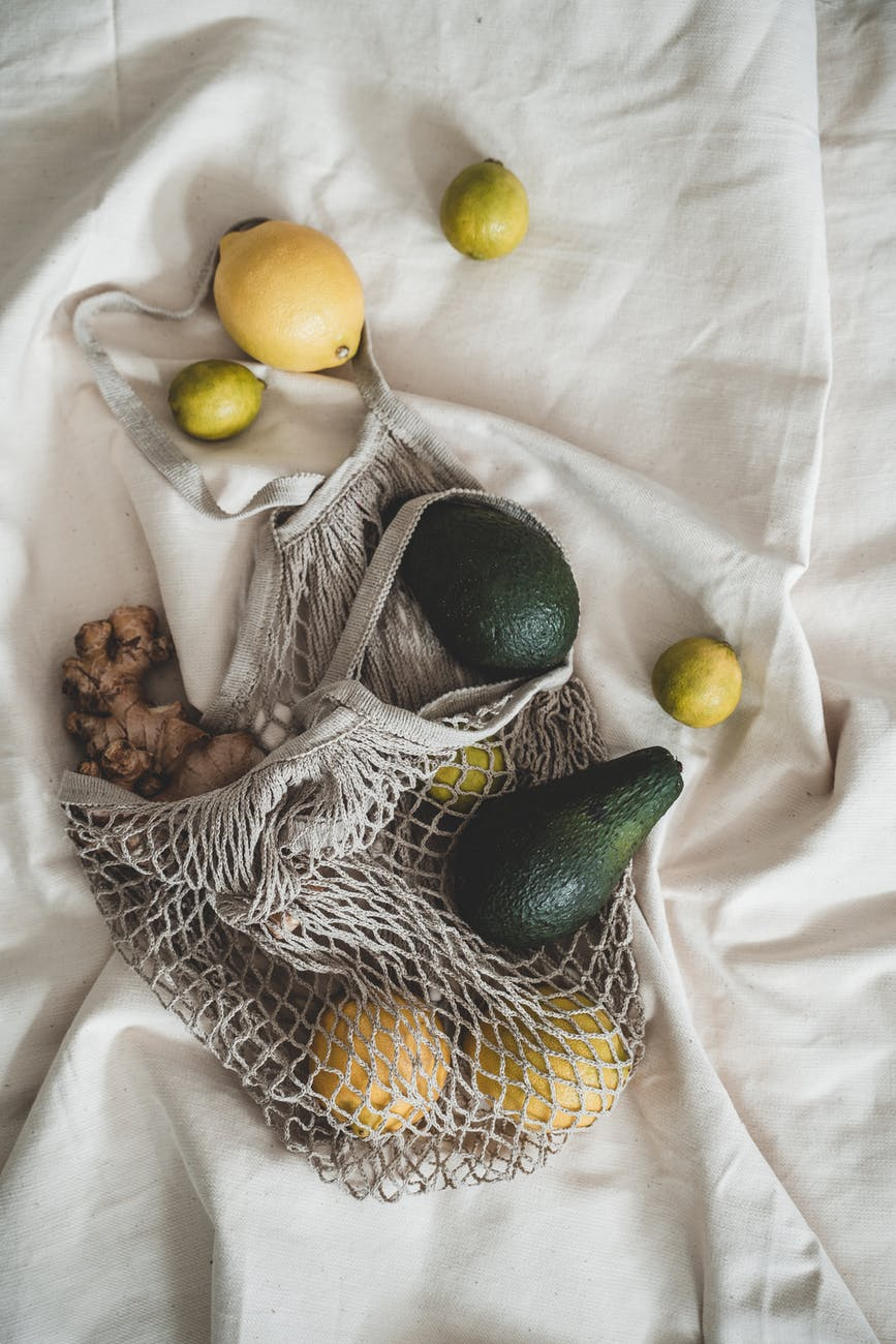 A woven fabric bag full of fruit and veggies