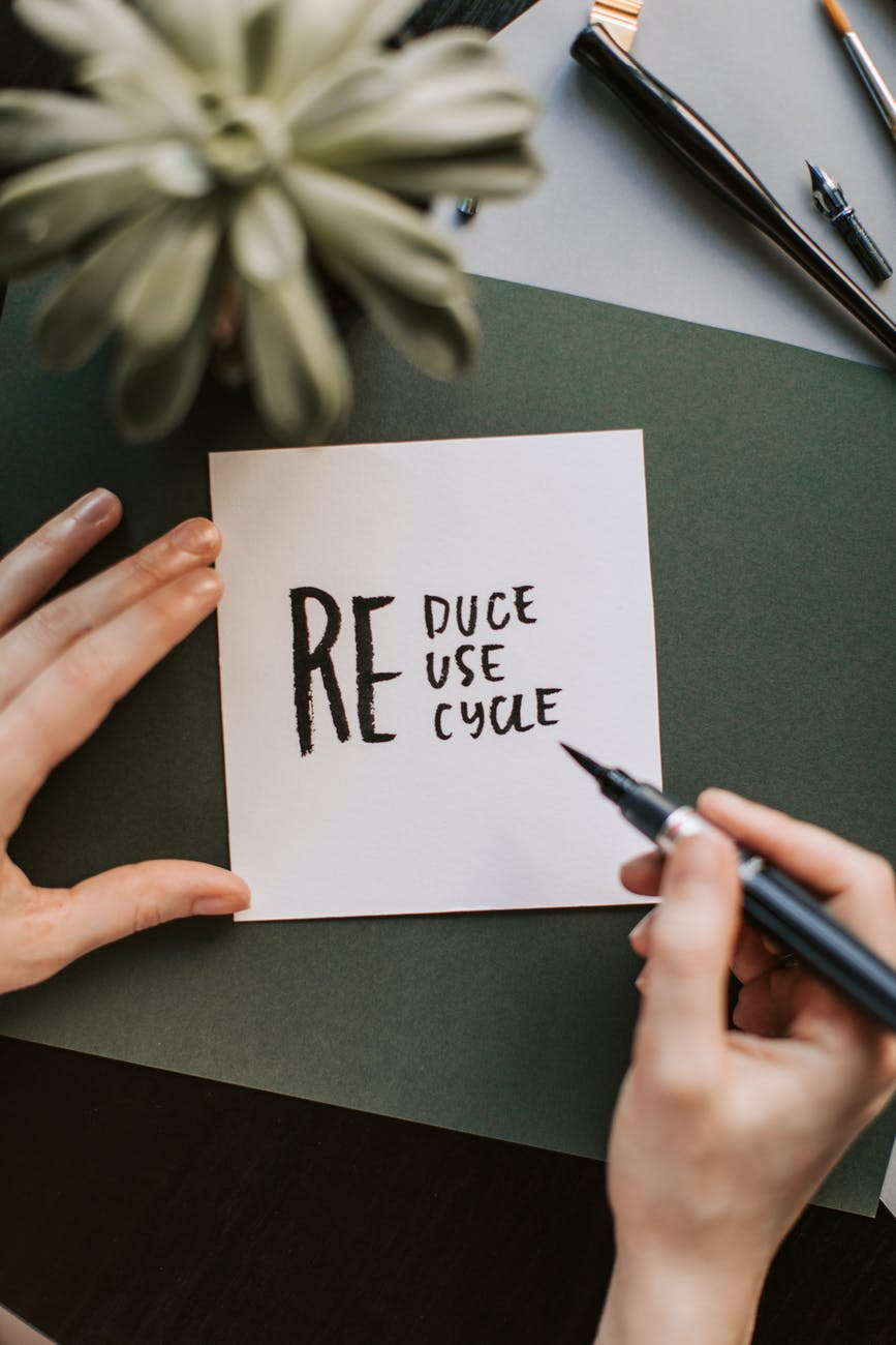 Some holding a pen over a paper that reads 'reduce, reuse, recycle'