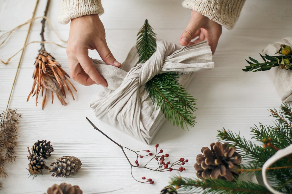 Florist preparing zero waste Christmas gift. Plastic free holidays. Hands decorating stylish christmas gift in linen fabric with green fir branch on white rustic table with pine cones and berries.